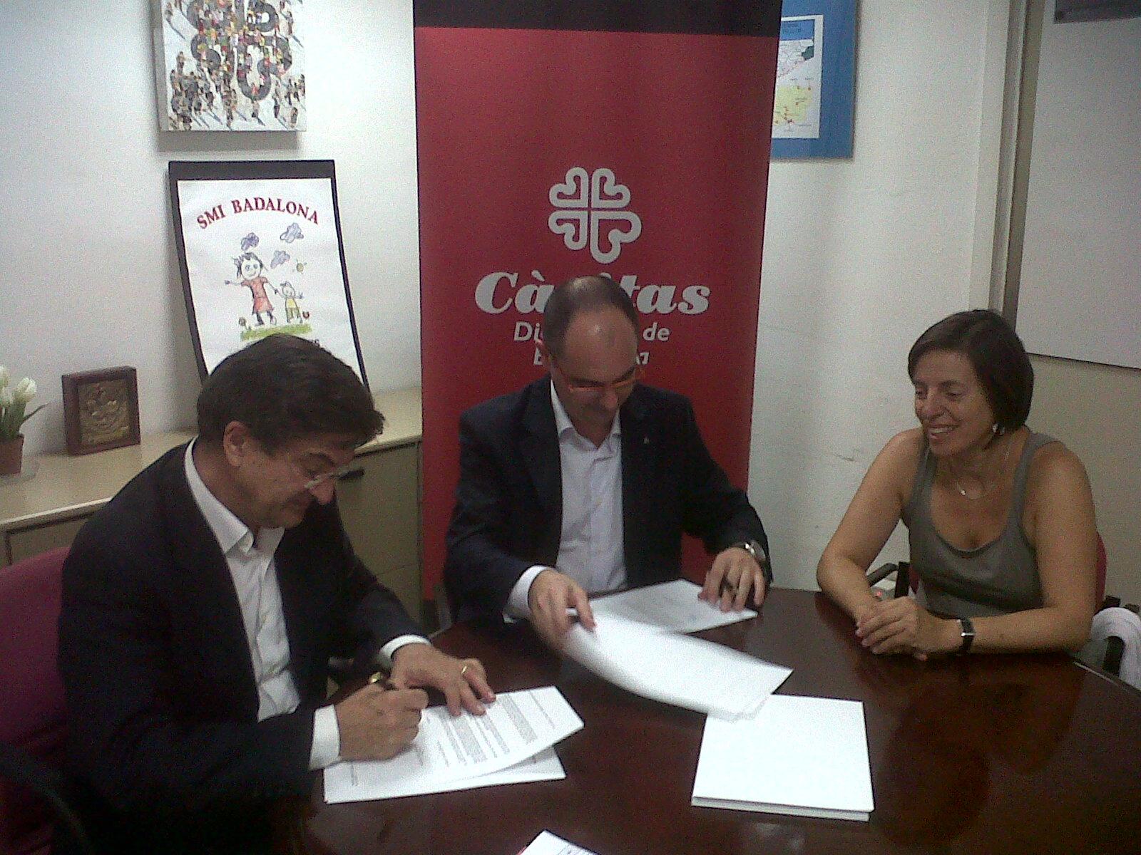 Imatge de la signatura del conveni entre la FAC i Càritas.