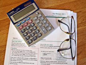 Una calculadora sobre una factura en paper. Font: Images_of_Money (flickr.com)