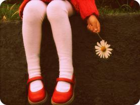 Fotografia d'una nena amb una margarita. Galeria de Just Luh a Flickr.