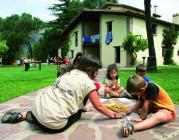Fotografia de nens jugant a terra, davant una casa de colònies
