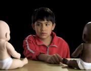 Fotograma amb un nen davant 2 ninots del vídeo de la campanya Racismo en México