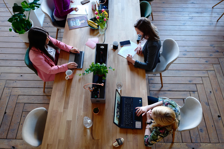 Tres treballadores que fan servir l'ordinador o el mòbil Font: Pexels