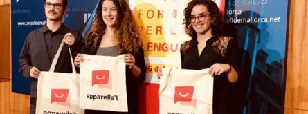 Tres participants en la iniciativa mostren bosses de roba amb el seu logotip