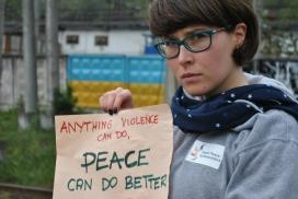Aga Stajer amb un cartell que diu en anglès: Qualsevol cosa que pugui fer la violència, la pau la pot fer millor