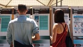 Dues persones presencien una exposició fotogràfica sobre persones refugiades.