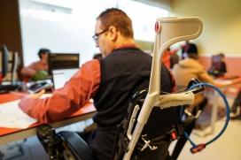 Noi amb cadira de rodes treballant en un ordinador