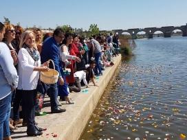 Persones llançant pètals al riu per celebrar el 8 d'abril, Dia Internacional del Poble Gitano