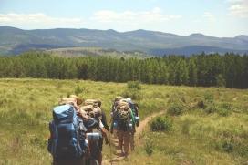 Un grup de joves d'excursió per un prat, carregant motxilles, en el marc d'una activitat d'educació en el lleure