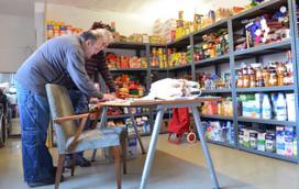 Dues persones voluntàries del centre El Caliu gestionant el rebost i les donacions d'aliments