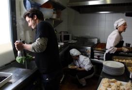 Un dels clients de La Trobada de Terrassa ajudant dues de les cuineres (ACN)