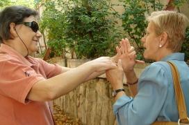 Una dona cega i sorda comunicant-se amb el sistema dactilològic. Font: ONCE