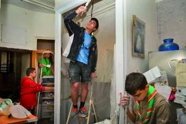 Un grup de joves escoltes fent tasques de rehabilitació d'un habitatge.