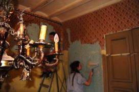 Una jove escolta pintant la paret d'un habitatge.