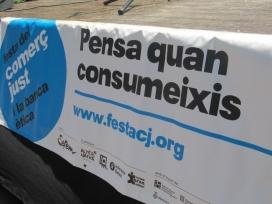 """Pancarta de la Festa del Comerç Just: """"Pensa quan consumeixis"""""""