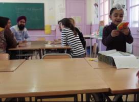 Una família reunida amb les impulsores del projecte a una aula de l'escola