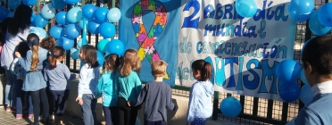 Infants celebrant el Dia mundial de conscienciació sobre l'autisme, amb una pancarta i globus blaus.
