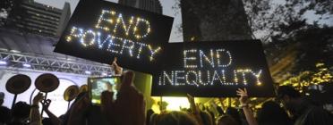 """Una manifestació multitudinària on destaquen dues pancartes que diuen en anglès: """"Eradiquem de la pobresa"""" i """"Eradiquem la desigualtat"""""""