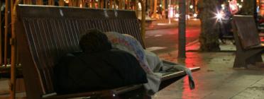 Persona sense llar dorm al carrer enmig de la nit.
