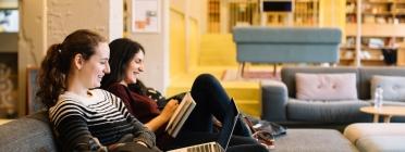 Dues dones assegures a un sofà rient