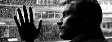 Un jove mira per la finestra en un dia plujós