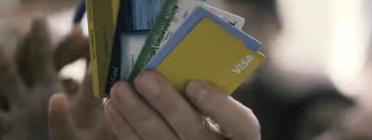 Fotograma del vídeo de la campanya que mostra unes targetes bancàries en una mà