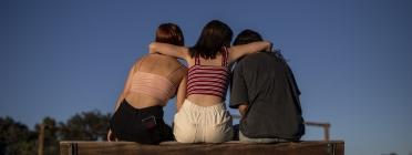 Escena representada: tres noies seuen a un banc donant-se suport. Font: Save The Children