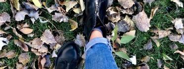 Persona caminant amb botes negres sobre un terra ple de fulles