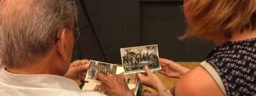 Fotograma del vídeo de Betevé: Lliberat Hosta i la reportera miren fotografies antigues