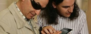 Una persona voluntària acompanyant a una persona amb discapacitat visual, usuària de l'ONCE