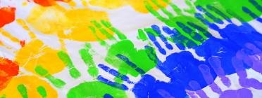 Imatge d'un mural pintat amb mans de diferents colors