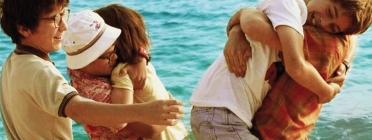 Una colla d'amics i amigues jugant i abraçant-se a la platja durant les vacances d'estiu