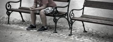 jove adolescent mirant el mòbil assegut en un banc de fusta
