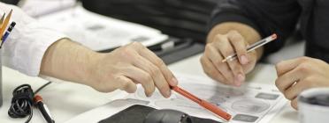 Home i dona amb mans damunt la taula explicant sobre el paper temes de formació
