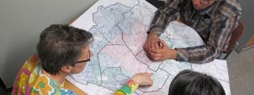 Persones mirant mapa a sobre d'una taula