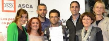 Membres de la cooperativa Tapurna ensenyant el premi que van rebre al 2014