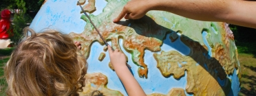 Un nen observa la bola del món. Font: Max Pixel, Free Great Picture