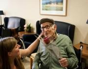Una voluntària regalant-li una rosa a una persona gran. Font: AGG