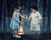 Una nena li dóna una flor al seu company.