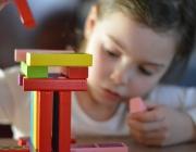 Una nena juga amb un joc de construcció.