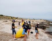 Un grup d'infants escoltes netejant un fragment de costa durant la campanya Clean up the Med