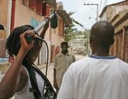 Periodistes amb càmera i micròfon gravant una escena del reportatge.