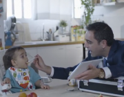 Fotograma del vídeo 'El meu primer verí'. Un home dona a menjar un potet a un nadó, mentre l'entreté amb una tauleta