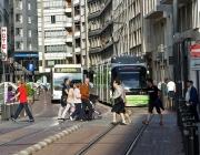 Carrer ciutat amb tramvia i bus