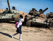 Amal al Torchani, una nena d'11 anys que en la imatge camina davant dos tancs aturats. És el camí que ha de fer per anar a l'escola, a Misrata, Líbia (Font: flickr.com - Autor: Jordi Bernabeu Farrús)