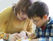 Una voluntària ajudant a llegir a un nen