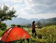 Noia llegint dempeus fora de la tenda de campanya en un entorn de muntanyes