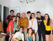 Un grup de joves escoltes amb el propietari de l'habitatge rehabilitat durant La Murga 2017