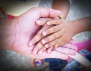 Man d'infants a sobre del palmell d'una mà adulta