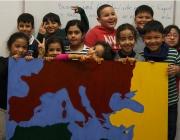 Els nens i nenes que participen al projecte mostren un mapa que han creat