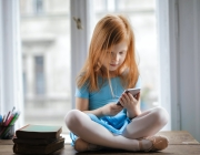 Una nena es mira un telèfon mòbil. Font: Andrea Piacquadio (Pexels)